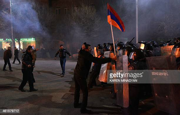 A man holds an Armenian flag up as protesters clash with police during a demonstration near the Russian Consulate General in Gyumri northwestern...