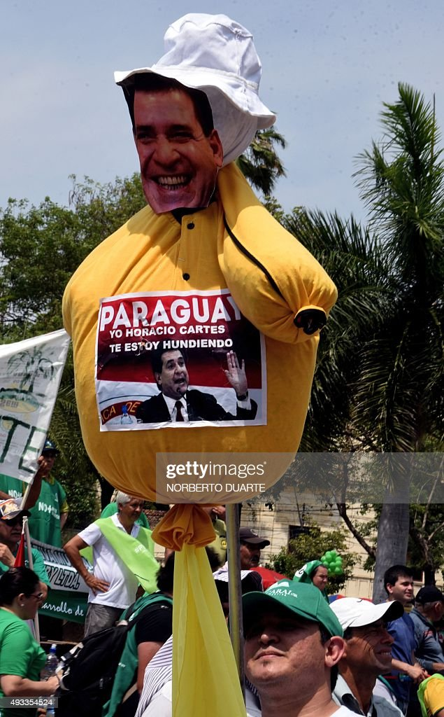 A man holds an effigy of Paraguayan President Horacio Cartes during a demonstration against a new tax law in Asuncion on October 19 2015 The...