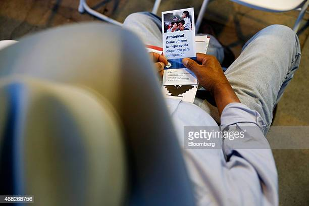 A man holds an informational brochure during an immigration workshop held in the back yard of a home in Hanford California US on Thursday March 19...