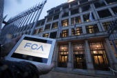 A man holds an ipad showing the new logo of 'Fiat Chrysler Automobiles' on January 29 2014 in front of Fiat headquarter at Lingotto in Turin Italian...
