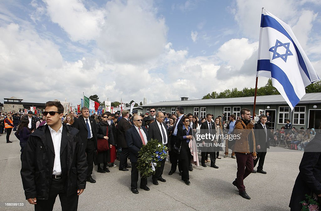 A man holds an Israeli flag as people commemorate the liberation of the Nazi concentration camp Mauthausen on May 12, 2013, 160 kilometers near Vienna.