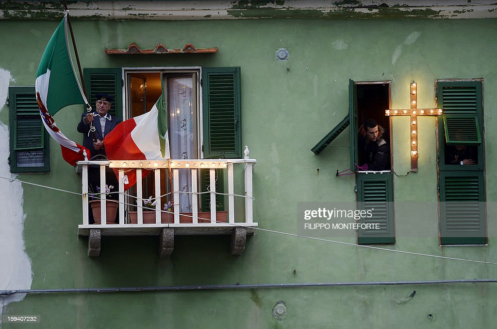 A man holds an Italian flag on his balcony overlooking the port in the Italian island of Giglio on January 13, 2013. Survivors, grieving relatives and locals on the island of Giglio gathered on January 13 to mark the first anniversary of the Costa Concordia cruise ship disaster, which claimed 32 victims. AFP PHOTO / FILIPPO MONTEFORTE
