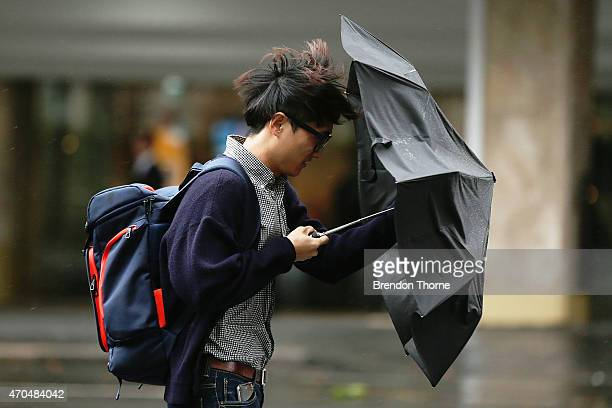 A man holds an umbrella against strong winds in the CBD on April 21 2015 in Sydney Australia A second day of damaging winds and heavy rain have hit...