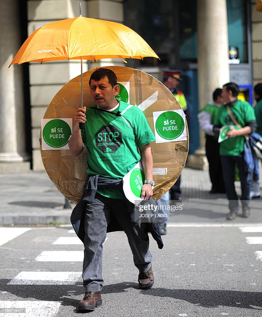 A man holds an umbrella and a placard reading 'Yes we can' during a protest by Platform for Mortgage Victims (PAH) to push for a new law to end a wave of evictions of homeowners ruined by the economic crisis, in Barcelona, on March 27, 2013.