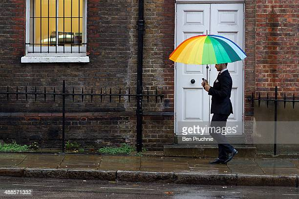 A man holds an umbrella as he shelters from the rain on September 16 2015 in London England Tropical Storm Henri has been downgraded to an extropical...