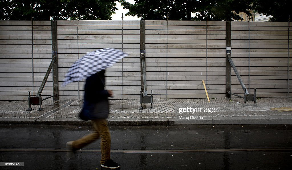 A man holds an umbrella as he walks past anti-flood barriers along the Vltava River on June 3, 2013 in Prague, Czech Republic. The Czech government has declared a nationwide state of emergency after days of heavy rainfall continue to cause severe flooding. Flood defences have been erected to protect Prague's historic center and people have been evacuated from low-lying areas. At least four people are feared to have been killed and several are missing as rivers continue to rise throughout many regions in Bohemia.