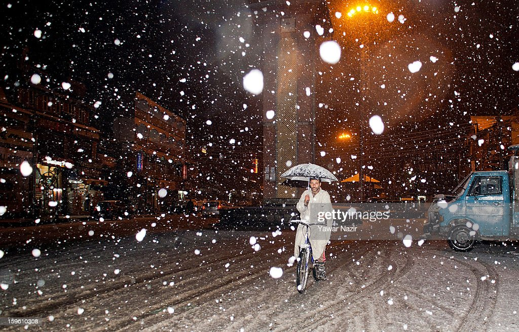 A man holds an umbrella whilst riding a bicycle during heavy snowfall on January 17, 2013 in Srinagar, Indian Administered Kashmir, India. Several parts of the Kashmir Valley, including the summer capital Srinagar, experienced fresh snowfall today, prompting the authorities to issue an avalanche warning and leading to closure of the Jammu-Srinagar Highway, the only road link between Kashmir and rest of India.