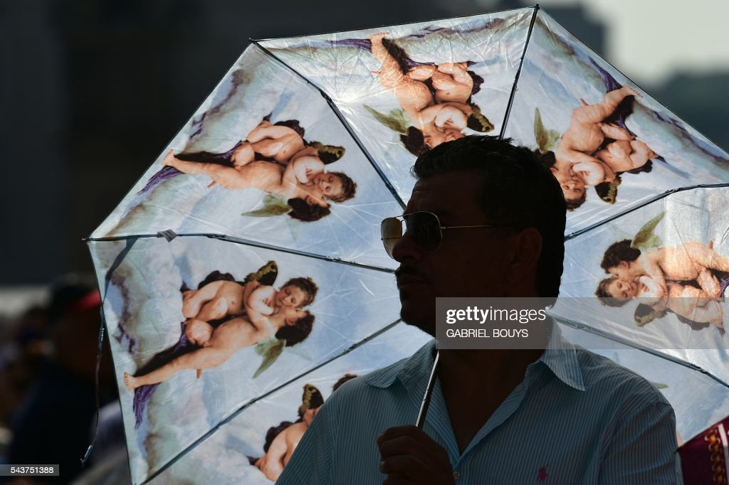 A man holds an umbrella with angels printed on during Pope Francis Jubilee audience at St Peter's square on June 30, 2016 in Vatican. / AFP / GABRIEL