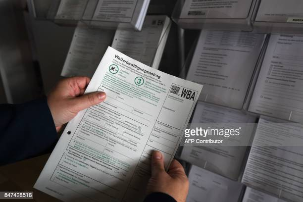 A man holds an unemployment benefits application form at the Jobcenter in DuesseldorfMitte western Germany on August 25 2017 The number of people out...
