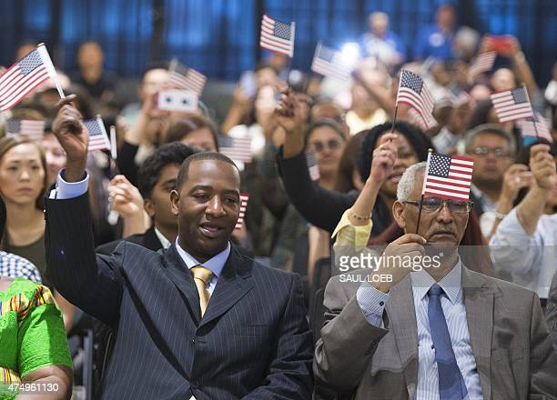 A man holds an US flag prior to taking the citizenship oath to become a US citizen during a naturalization ceremony at the US Patent and Trademark...