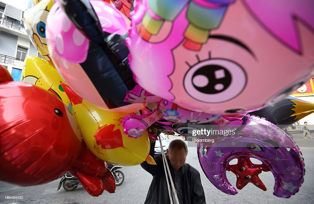 A man holds balloons on a street in Wuhan, China, on Sunday, Oct. 20, 2013. China's economic expansion accelerated to 7.8 percent in the third quarter from a year earlier, the statistics bureau said Oct. 18, reversing a slowdown that put the government at risk of missing its 7.5 percent growth target for 2013. Photographer: Tomohiro Ohsumi/Bloomberg via Getty Images
