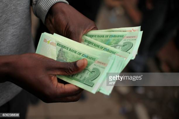 A man holds bond notes released by the Reserve Bank Of Zimbabwe in Harare central business centre on November 28 2016 Zimbabwe issues 'bond notes'...