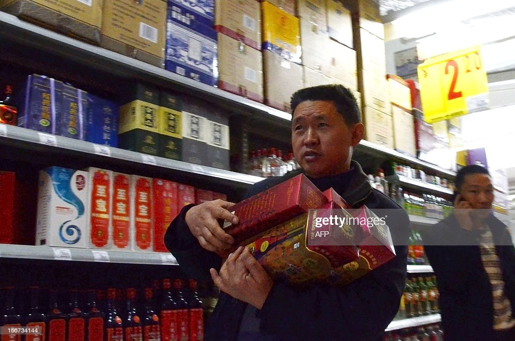 A man holds bottles of white spirit as he walks in a supermarket in Beijing on November 20, 2012. China Alcoholic Drinks Association said all Chinese 'White spirit' had plasticizer. AFP PHOTO WANG ZHAO