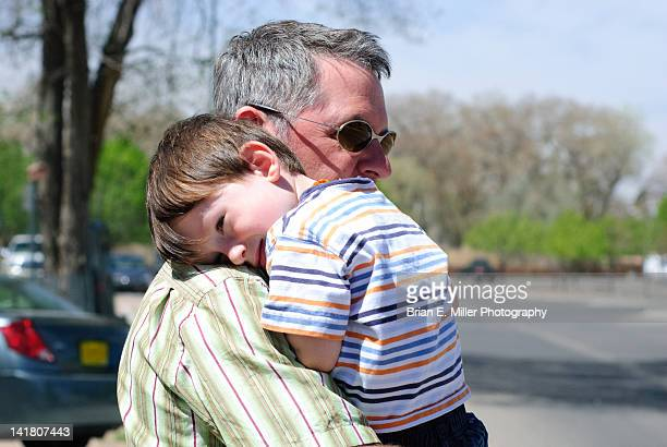 Man holds boy in arms