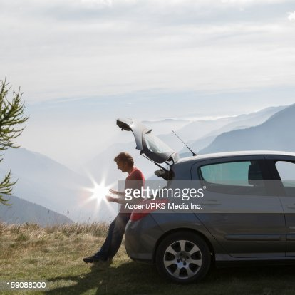 Man holds burst of sunshine from tail of car, mtns : Stock Photo