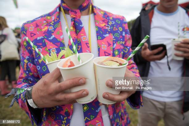 A man holds cocktails at Glastonbury Festival Worthy Farm Somerset PRESS ASSOCIATION Photo Picture date Sunday June 2017 Photo credit should read Ben...