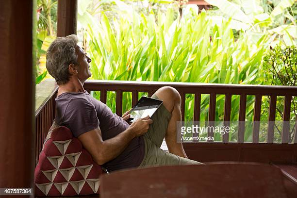 Man holds digital tablet, looks out to jungle