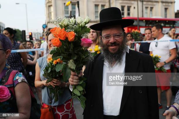 A man holds flowers as he attends a vigil outside Finsbury Park Mosque on June 19 2017 in London England Worshippers were struck by a hired van as...