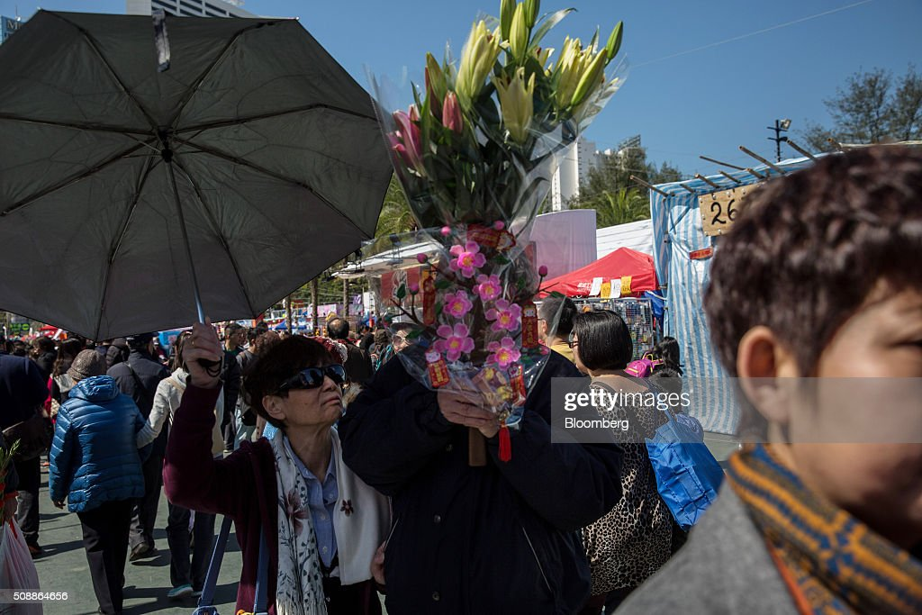 A man holds flowers as he walks past stalls at the Lunar New Year fair in Victoria Park in Hong Kong, China, on Sunday, Feb 7, 2016. The city's financial markets will close on Feb. 8 for the Lunar New Year holidays and resume trading on Feb. 11. Photographer: Billy H.C. Kwok/Bloomberg via Getty Images
