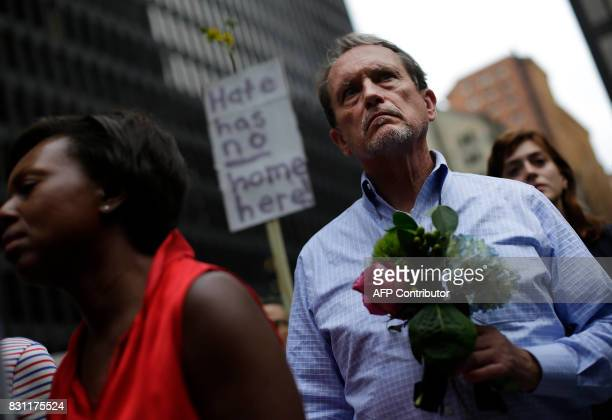 A man holds flowers at a vigil August 13 2017 in Chicago Illinois for the victims in the previous day's violent clashes in Charlottesville Virginia...