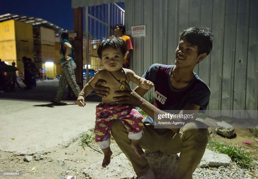 Man holds his baby at a construction workers' camp on May 6, 2016 in Bangkok, Thailand. Mainly migrants from neighboring countries, like Cambodia and Laos, live in this camp, which has grocery shops, a common washing area and even a small school, on the outskirts of Bangkok.