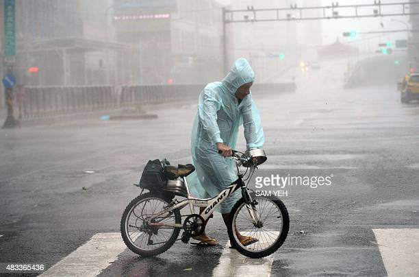 A man holds his bike as typhoon Soudelor hits Taipei on August 8 2015 Typhoon Soudelor battered Taiwan with fierce winds and rain leaving four people...
