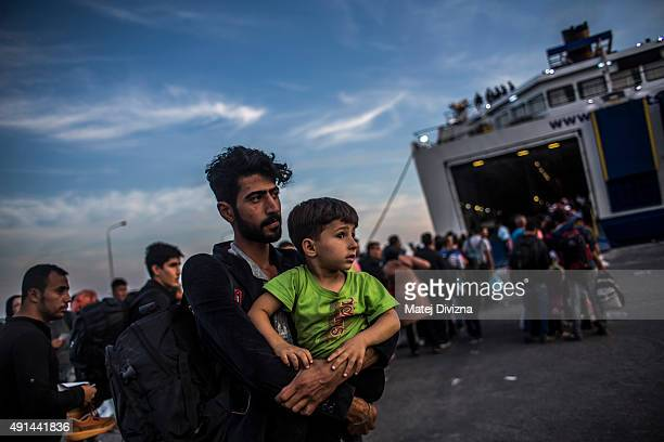 A man holds his boy as other refugees and migrants line up to board a ferry after arriving on the shores of the Greek island of Lesbos after crossing...
