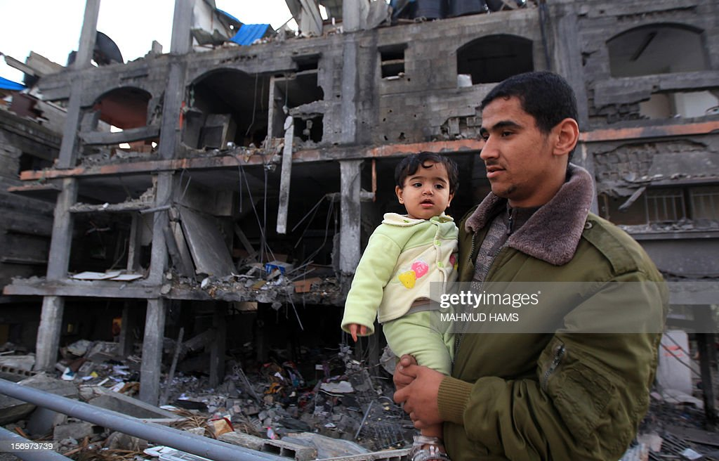 A man holds his child as he walks past destroyed buildings in Beit Lahia, in the northern Gaza Strip, on November 26, 2012, following a truce last week between Israel and Hamas that ended eight days of conflict in which 166 Palestinians and six Israelis were killed.