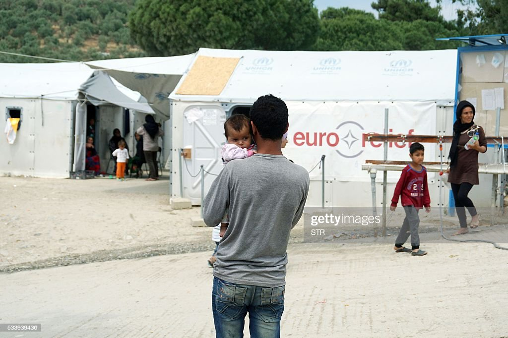 A man holds his child at the Moria detention camp for migrants and refugees at the island of Lesbos on May 24, 2016. So far this year, the International Organisation for Migration says an estimated 190,000 migrants and refugees have entered Europe by sea, arriving in Italy, Greece, Cyprus and Spain. Another 1,359 have died en route. / AFP / STR