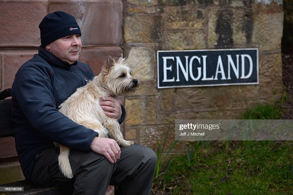 A man holds his dog as he sits on a bench next to the Union Bridge on the River Tweed on March 6, 2013 in Berwick Upon Tweed, England. The bridge was built in 1820 and is Europe's oldest surviving iron chain suspension bridge. The bridge which connects the Scottish village of Fishwick to Horncliffe on the English bank is now facing closure with both Scottish Borders Council and Northumberland, citing a £4.7million repair bill for the structure.