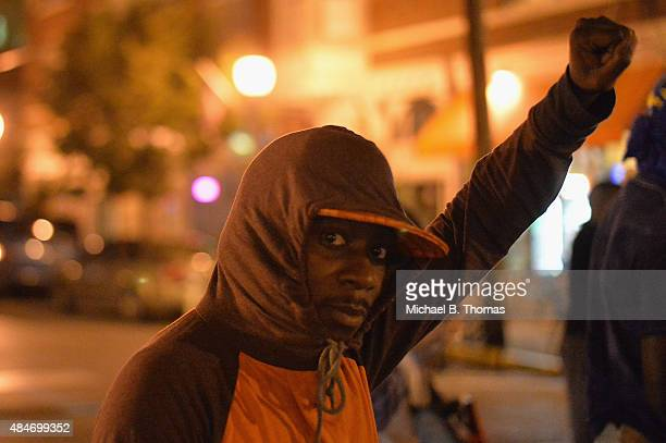 A man holds his fist in the air during a protest action through the Central West End of St Louis Missouri on August 20 2015 After a night of unrest...