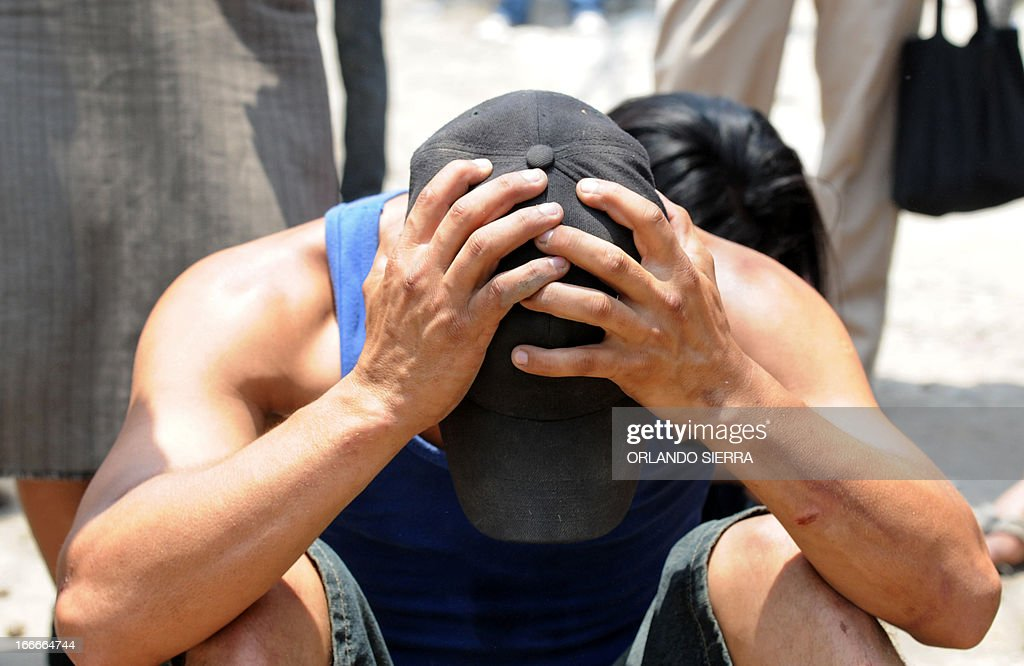 A man holds his head at the crime scene in which five people -- including a high school student -- were shot dead in the suburb of La Haya, in northern Tegucigalpa, on April 15, 2013. In March 2012, the UN announced Honduras had the world's highest murder rate, at 82.1 deaths per 100,000 people, while a local observatory on violence put the rate at 86.5 per 100,000. AFP PHOTO/Orlando SIERRA