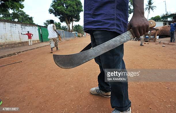 A man holds his machete as young people who created a selfdefence committee for their district Benzvi met before leaving for a patrol in their...