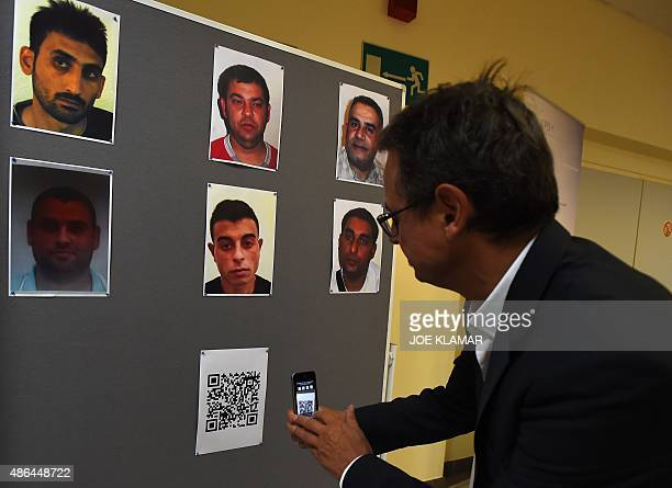 A man holds his smartphone in front of a barcode link under the pictures of suspected human traffickers arrested over the death of 71 refugees found...