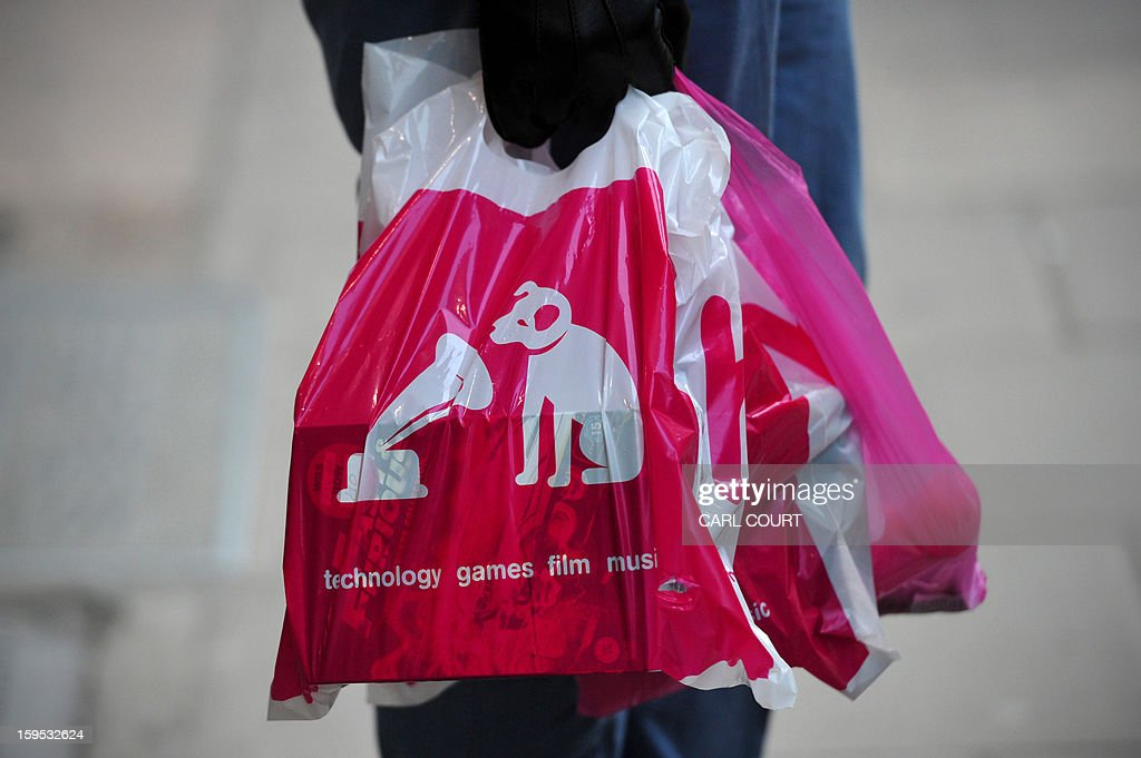 A man holds HMV bags outside a branch of the music retailer in central London on January 15, 2013. Iconic British music retailer HMV was fighting for its survival on Tuesday after the group looked to the Deloitte financial group to help save it from a collapse which could see the loss of more than 4,000 jobs.AFP PHOTO / CARL COURT