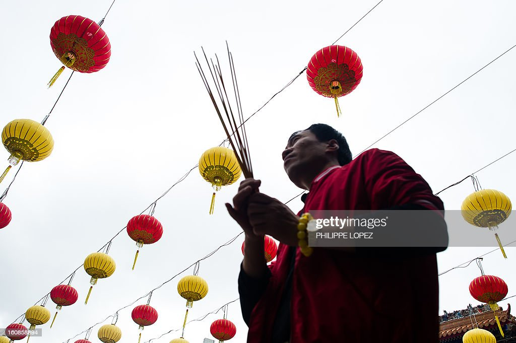 A man holds incense sticks under a display of lanterns at a Taoist temple in Hong Kong in Hong Kong on February 7, 2013. A stock market slide, escalated conflict between Japan and China and more Gangnam-styled success for South Korean singer Psy will shape the incoming Year of the Snake, say Asian soothsayers. February 10 marks the first day of the Lunar New Year across the region. AFP PHOTO / Philippe Lopez
