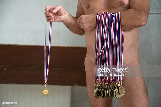 A man holds medals during a naturist swimming championship on October 25 2014 in Mulhouse eastern France AFP PHOTO / SEBASTIEN BOZON