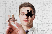 Man holds missing jigsaw piece for his face