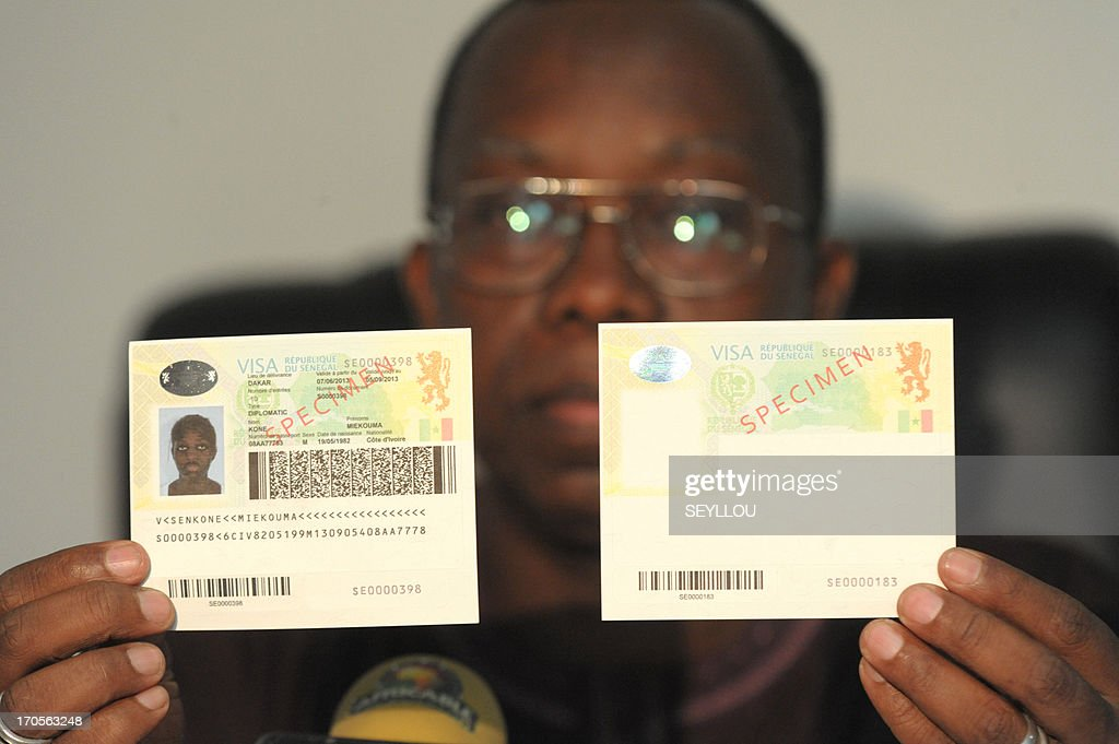 A man holds on June 14, 2013 specimens of the new Senegalese biometric visa that will be launched on July 1, 2013. AFP PHOTO / SEYLLOU