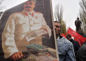 A man holds on November 7 2013 a portrait of Soviet dictator Joseph Stalin in front of the Lenin monument in Kiev during a Communist Party rally to...