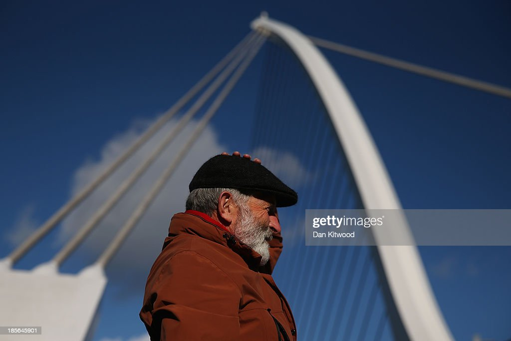 A man holds on to his hat in high winds as he waits for friends under the Samuel Beckett Bridge on October 23, 2013 in Dublin, Ireland. The bridge was designed by Santiago Calatrava and opened in 2009. It connects the north and south sides of the River Liffey. Dublin is the capital city of The Republic of Ireland situated in the province of Leinster at the mouth of the River Liffey. The greater Dublin area has a population of around 1.5 Million people.