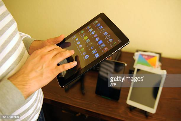 A man holds one of the Armenia's first tablet computers ArmTabs designed by the joint ArmenianUS company Minno in Yerevan on March 18 2014 Designed...