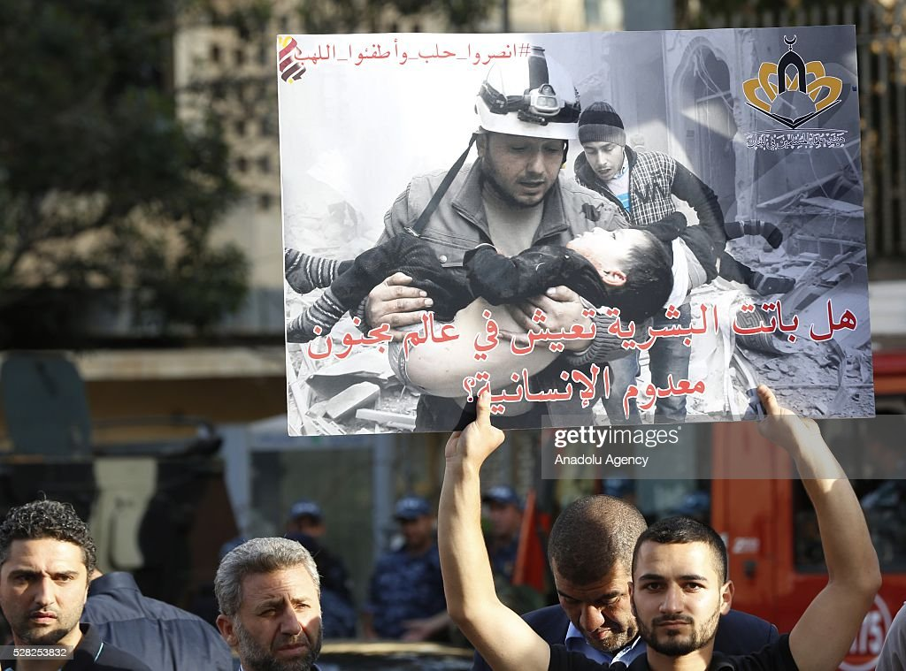 A man holds picture of victim as a group of Muslim scholars hold signs reading in 'Aleppo is burning, Help Aleppo' and protest against the air strikes conducted by the Assad regime and Russia over the Aleppo in front of Russian embassy building in Beirut, Lebanon on May 4, 2016.