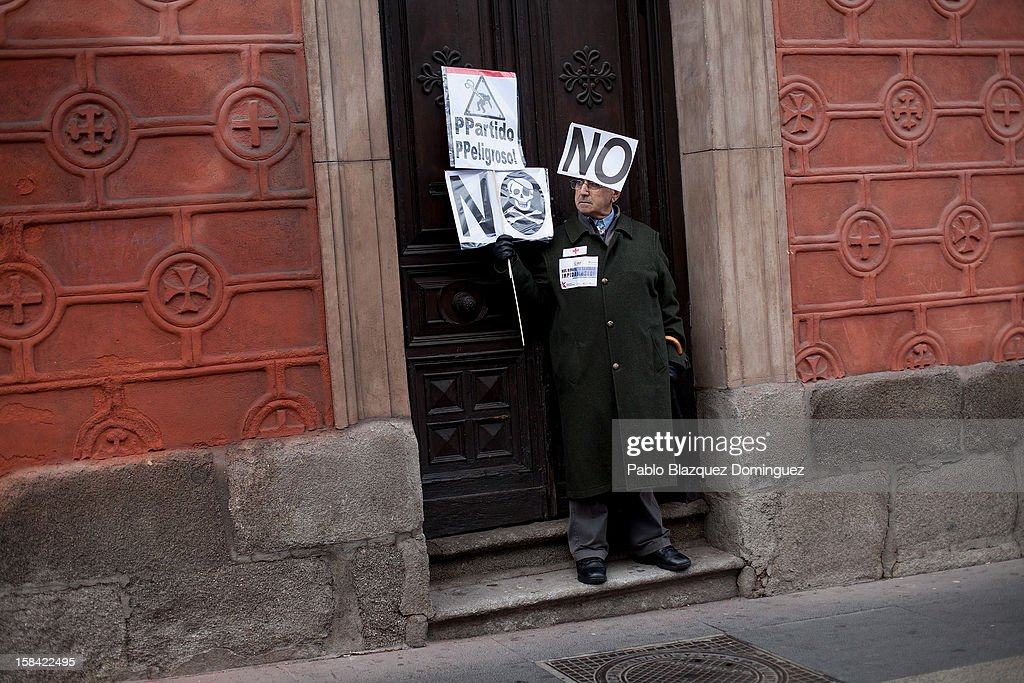 A man holds placards during a health workers demonstration against cuts on public health care and the privatization of medical centers and hospitals on December 16, 2012 in Madrid, Spain. In Madrid, doctors have already staged 11 days of strikes and all health workers unions are calling for a third 48 hour strike on December 19 and December 20. Around 4,000 operations have been suspended in Madrid since the medical strikes started.