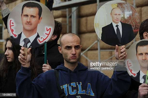 A man holds portrait of Russia's President Vladimir Putin and Syria's President Bashar alAssad during a rally in support of Syrian regime in front of...