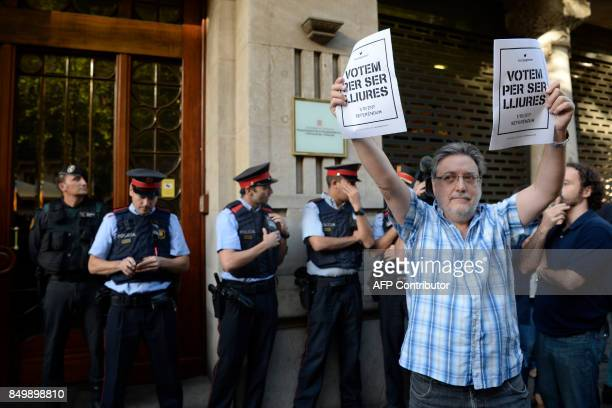 A man holds proreferendum posters reading in Catalan 'We vote to be free' as Spanish Civil Guards and Catalan regional police officers 'Mossos...