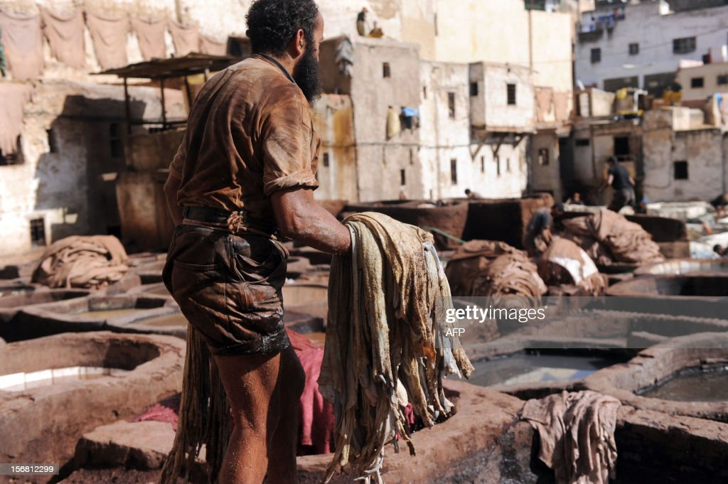 A man holds sheepskins at the tanneries in Fes on November 21, 2012. AFP / PHOTO / FADEL