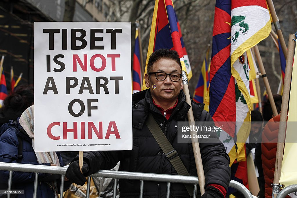 A man holds sign at a rally to mark the 55th anniversary of the Tibetan national uprising outside the United Nations buiding on March 10, 2014, in New York City. On this day in 1959, an uprising against China's occupation of the autonomous region of Tibet took place, forcing spiritual leader the Dalai Lama to flee into exile.