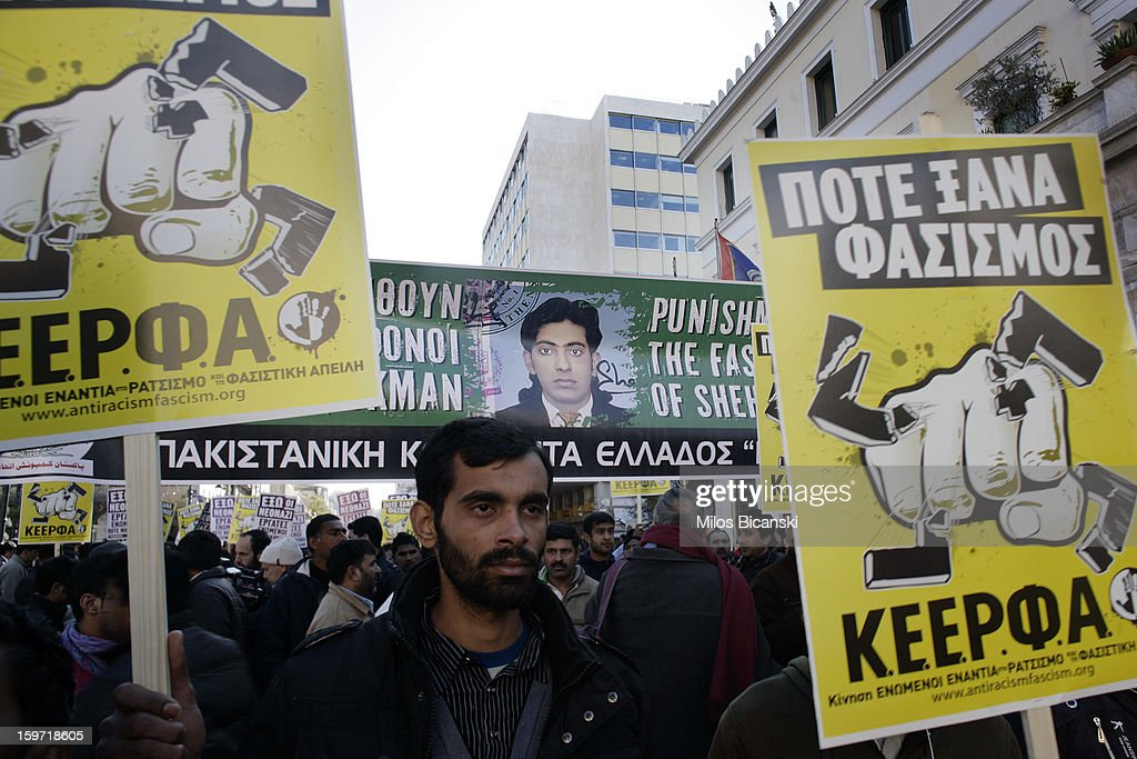 A man holds signs during a demonstration in response to the killing of 27-year-old Pakistani migrant who was a victim of an alleged racism-fuelled crime on January 19, 2013 in Athens, Greece. Hundreds of Greeks and other nationals marched peacefully against racism on January 19. Long standing as a hub for immigration from the Middle East, Africa and Asia, Greece is under pressure with racial issues as the economic crisis warps the burdens of blame in struggling communities.
