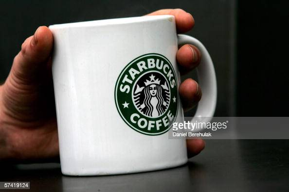 A man holds Starbucks Coffee mug in central London on April 25 2006 in London England The all traditional English style Breakfast 'FryUp' is under...
